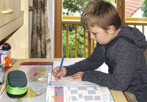 Kind auf Schreibtischstuhl macht Hausaufgaben